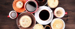 Many different cups of coffee on dark wooden table, top view.